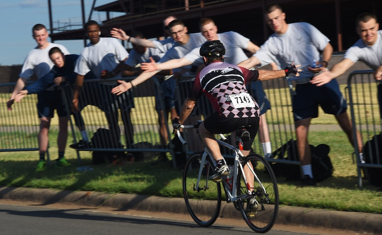 A Hotter'N Hell Hundred cyclist high-fives Airmen as he rides down Airmen's Alley at Sheppard Air Force Base, Texas