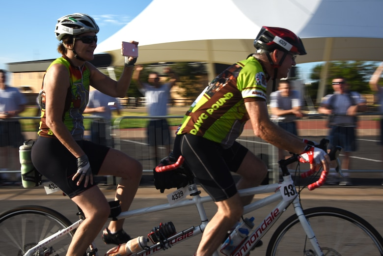 Hotter'N Hell Hundred cyclists ride a tandem bicycle and take photos of the Airmen cheering for them as they cruise down Airmen's Alley at Sheppard Air Force Base, Texas