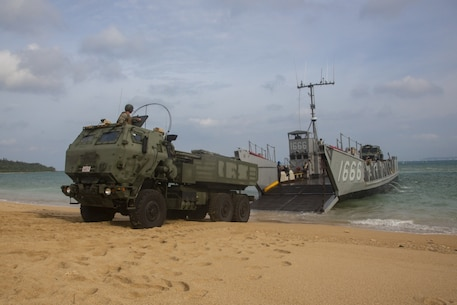 A landing craft, utility assigned to the amphibious transport dock ship USS Green Bay (LPD 20), lowers its ramp to unload a High Mobility Artillery Rocket System from 3rd Battalion, 12th Marine Regiment, 3rd Marine Division, as part of a simulated amphibious raid, at Kin Blue, Okinawa, Japan, Aug. 14, 2019. This simulated amphibious raid marks the first time that HIMARS have been inserted by landing craft, utility, demonstrating the Marine Air-Ground Task Force's ability to conduct combined-arms maneuver from amphibious shipping. (U.S. Marine Corps photo by Lance Cpl. Joshua Sechser)