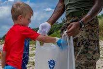 伊芸ビーチでのゴミ拾いに参加した児童が拾ったゴミをゴミ袋に入れるところ。アメリカ海兵隊員の家族の児童25人と6人の引率の大人が伊芸ビーチで清掃活動を行いました。