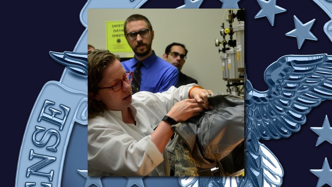 Sara Beth Erpel performs a leak test on military clothing in a lab with two other people looking on.