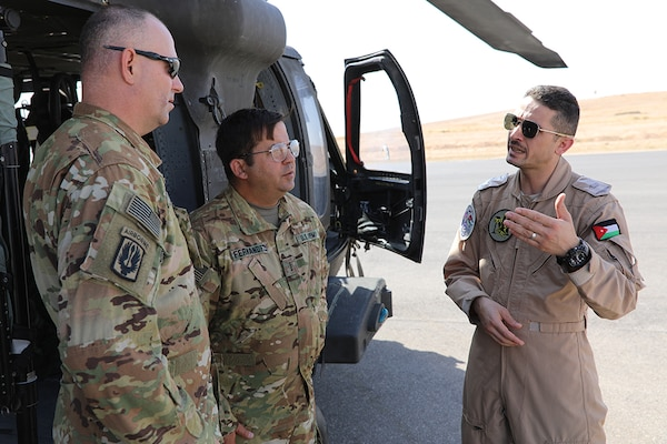Maj. Ibrahem Al-Zoubi, a UH-60 Black Hawk helicopter pilot from the Royal Jordanian Air Force's 30th Squadron, speaks with U.S. Army Chief Warrant Officer 4 Antonio Fernandez, center, and Chief Warrant Officer 2 Mark Sallin, both pilots with Task Force Javelin, prior to a local area of operation familiarization flight from an undisclosed location, Aug. 16, 2019. RJAF pilots assist U.S. Army pilots with local flight plans in preparation for TF Javelin's medical evacuation and air assault support during Eager Lion 2019.