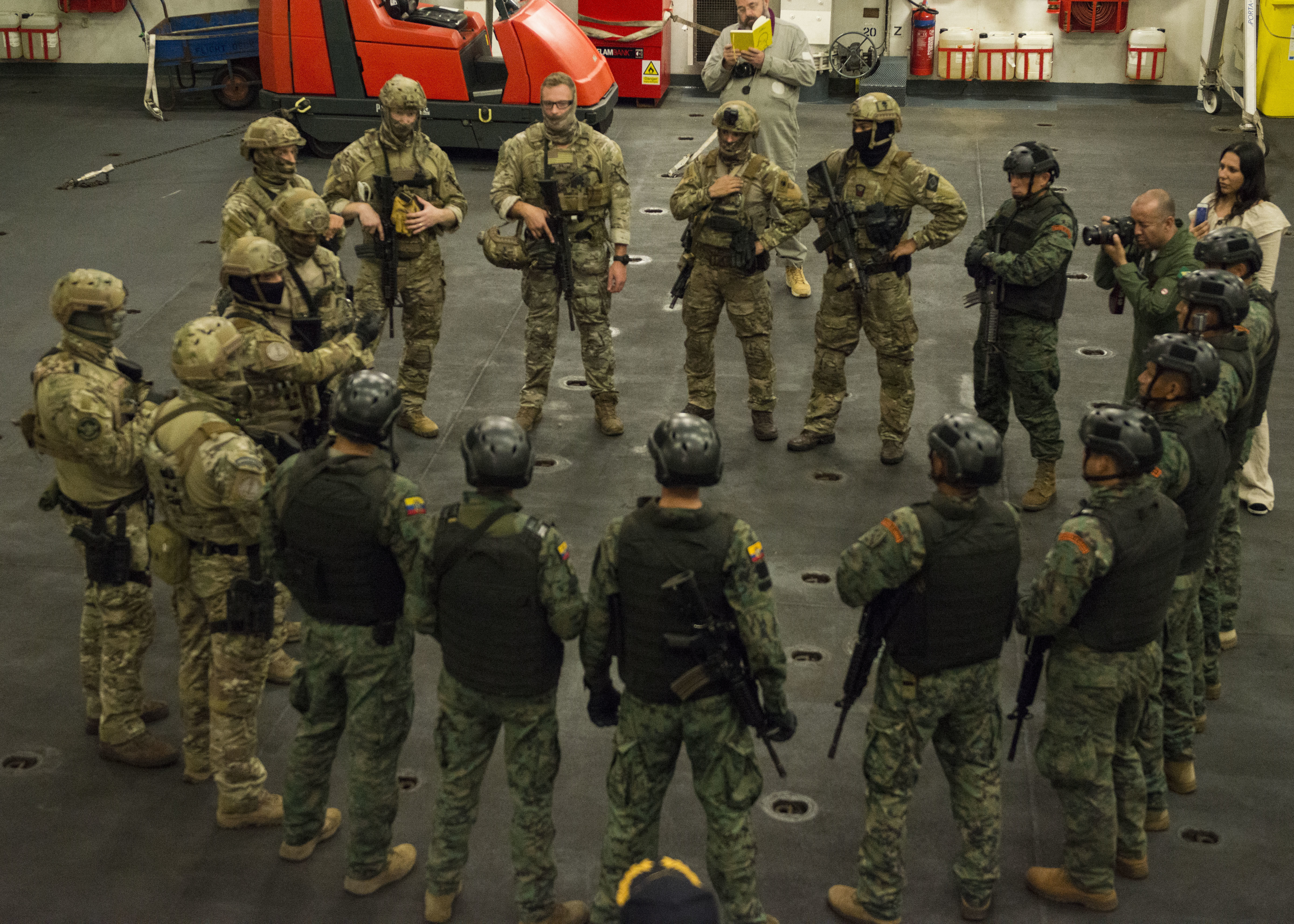 Military personnel gather in a group for a briefing.