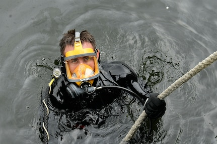 A diver emerges from the water.