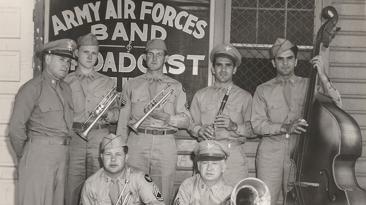 Members of the Army Air Corps Band pose for a photo after being broadcast to military members around the world. When the band recorded, the sound was captured on large recording lathes and a master vinyl disc was cut directly from the transmission.