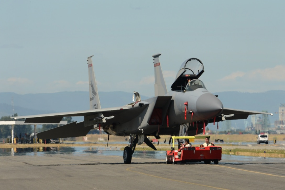 An Oregon Air National Guard F-15C Eagle, assigned to the 142nd Fighter Wing is tow from a maintenance hangar during dissimilar aircraft combat training (DACT) on Aug. 13, 2019, at the Portland Air National Guard Base, Ore. The Oregon Airmen are training with U.S. Navy F-18F Super Hornet from VFA-41 squadron, based out of Naval Air Station Lemoore, Calif., during two-weeks of DACT exercises. (U.S. Air National Guard photo by Master Sgt. John Hughel)