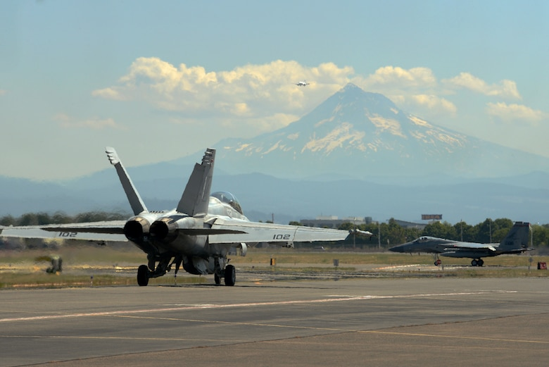 A U.S. Navy F-18F Super Hornet from VFA-41 squadron, based out of Naval Air Station Lemoore, Calif., taxis along the flightline with an F-15C Eagle, assigned to the 142nd Fighter Wing at the Portland Air National Guard Base, Portland, Ore., during an afternoon sortie as part of dissimilar aircraft combat training (DACT) on Aug. 13, 2019. The two-week training exercise from Aug. 11-23 provides realistic combat scenarios for pilots to hone advanced aerial tactics used against potential adversaries. (U.S. Air National Guard photo by Master Sgt. John Hughel)