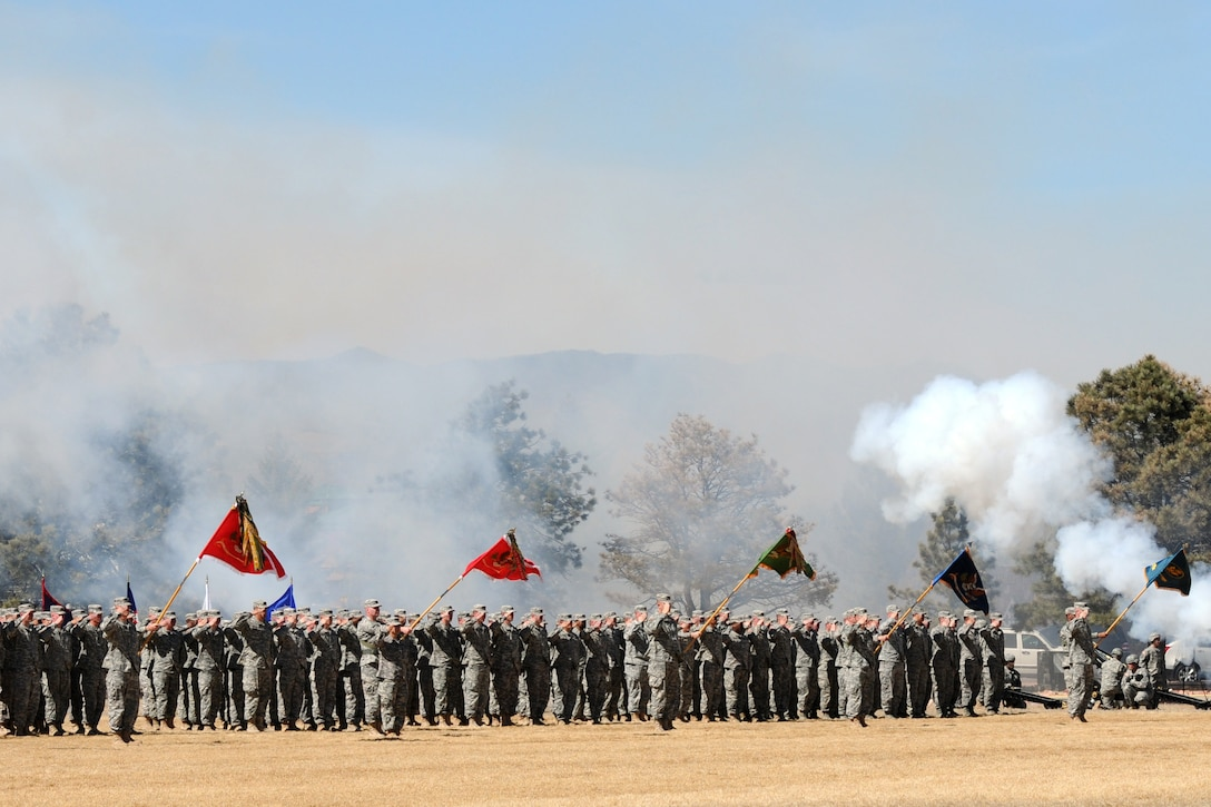 Smoke obscures a line of soldiers.