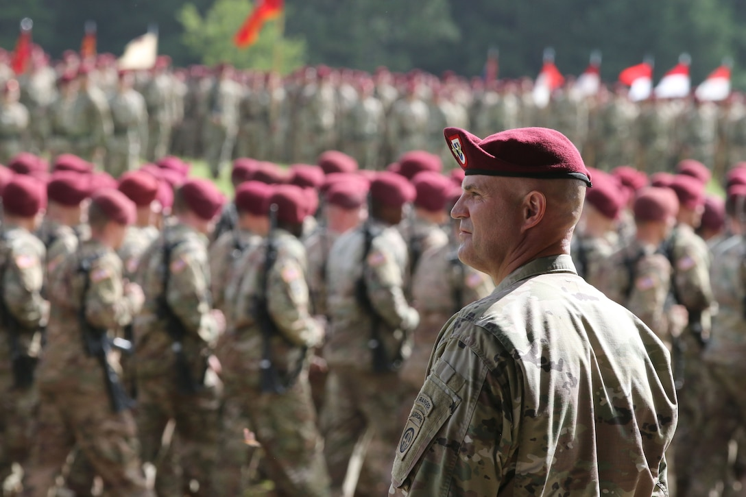 A soldier watches troops march in formation.