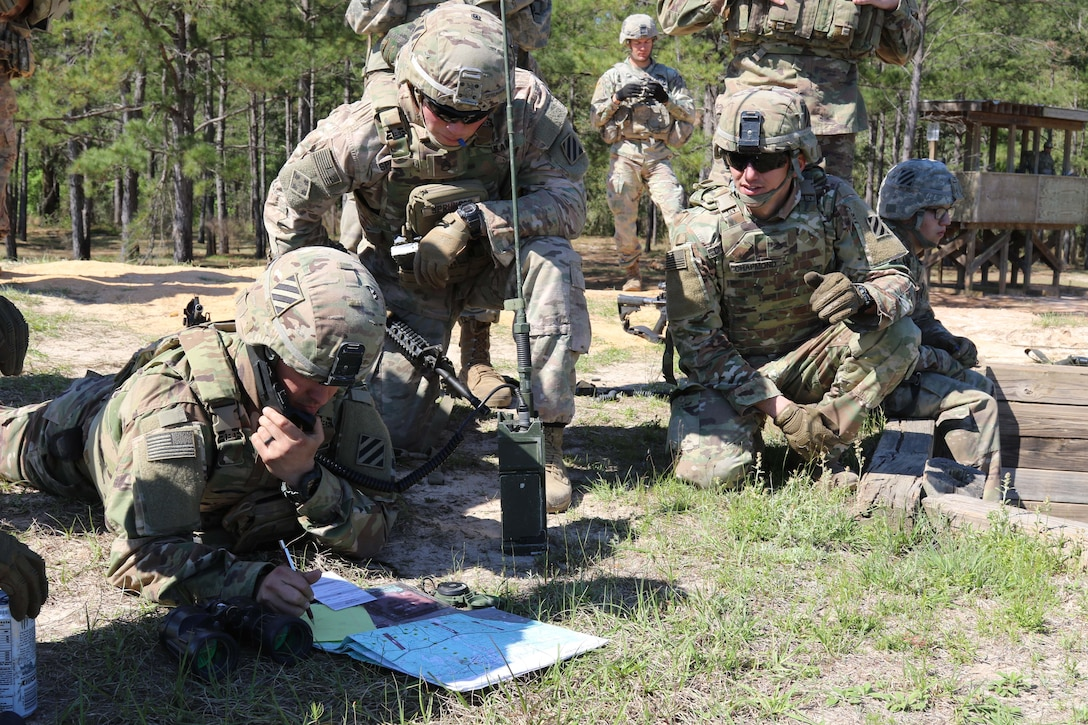 Three soldiers confer on the ground, using a map and communications equipment.