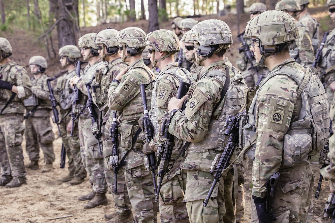 Soldiers stand in a group in a wooded area.