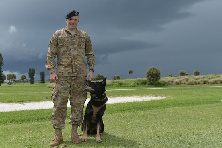 Staff Sgt. Avery Morehead, 45th Security Forces Squadron military working dog handler, and Military Working Dog, Tigi, pose for a photo at Patrick Air Force Base, Fla., August 6, 2019. Morehead was awarded the Life Saving Medal during the Melbourne Regional Chamber Valor Awards for his actions responding to a call at the Patrick AFB golf course. (U.S. Air Force photo by Airman 1st Class Dalton Williams)