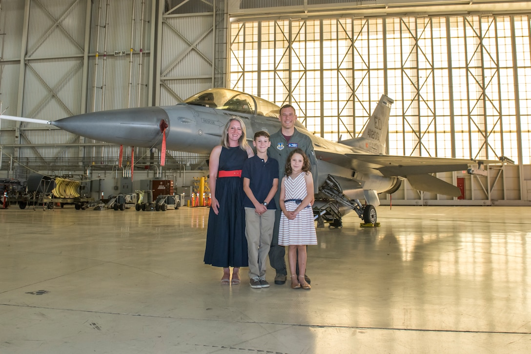 Family of Col. Timothy J. Spaulding gather to take a photo in front of the F16 now with Col. Spaulding's name on it during the change of command ceremony.