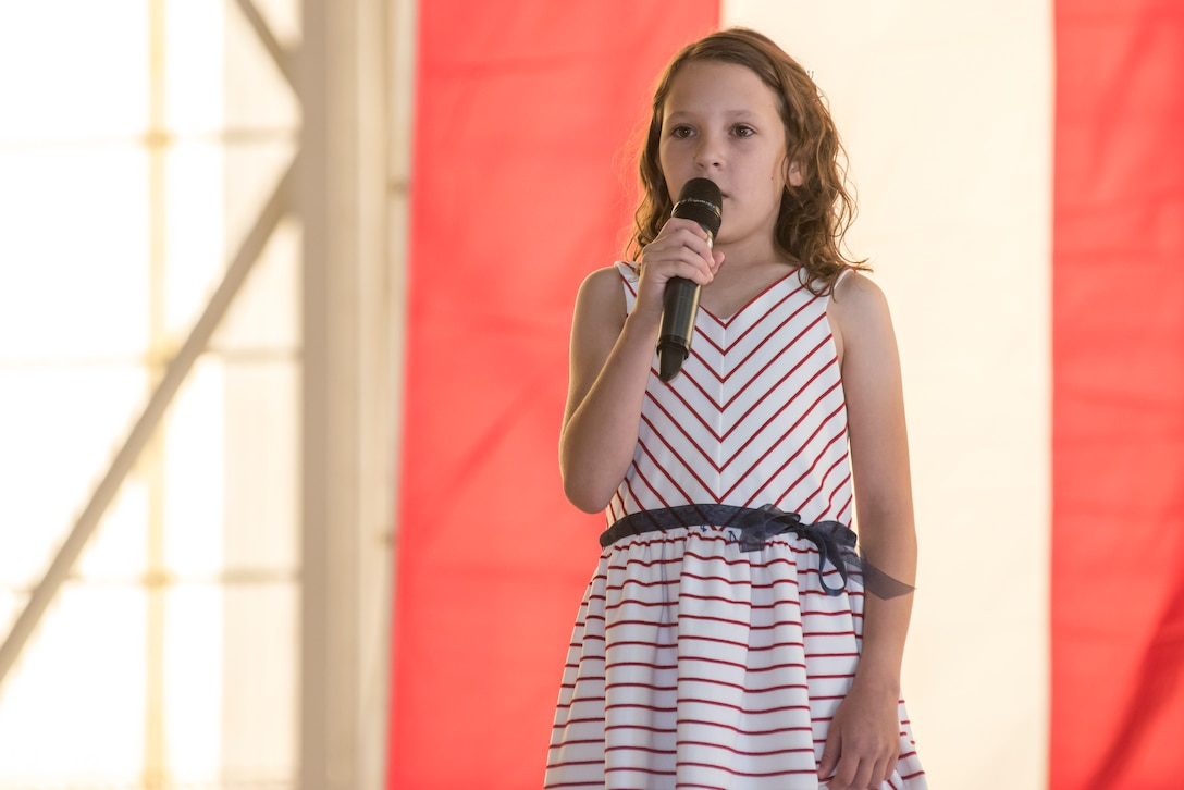 Daughter of Col. Timothy J. Spaulding sings the National Anthem during the change of command ceremony