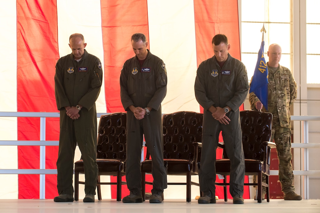 "Brig. Gen. E. John ""Dragon"" Teichert, Col. Christopher J. Spinelli and Col. Timothy J. Spaulding pray during the invocation by Lt. Col. Jason M. Botts."
