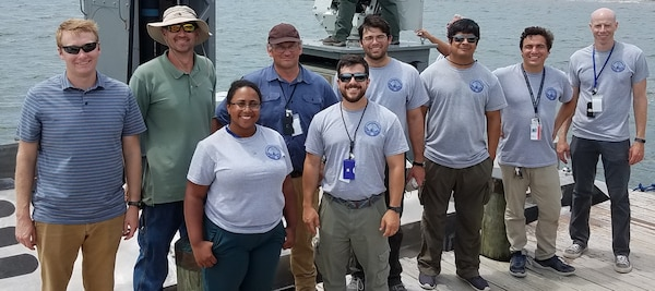 IMAGE: CAMP LEJEUNE, N.C. (July 19, 2019) — The Naval Surface Warfare Center Dahlgren Division (NSWCDD) Expeditionary Warfare Unmanned Surface Vessel (USV) team - pictured at the 2019 Advanced Naval Technology Exercise (ANTX) - demonstrated the Expeditionary Warfare USV's ability to control inshore and littoral areas while identifying and engaging remote targets at the exercise. The 40-foot self-driving boat is integrated with a HellFire Longbow missile system and a .50 gun mounted on a remote weapon station along with radar, video, and infrared systems. ANTX 2019 is an event where academic, industry and Navy participants test new and emerging technologies. NSWCDD scientists and engineers standing left to right are: Colin Pritchard, Adam Broad, Logan Camacho, Robert Gripshover, Kevin Green, Michael Teresi, Mark Manzano, Joseph 'Tripp' Cannella, and Michael Liska.  (U.S. Navy photo/Released)
