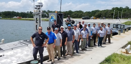 IMAGE: CAMP LEJEUNE, N.C. (July 19, 2019) — The Navy-industry Cooperative Research and Development Agreement (CRADA) team that developed the Expeditionary Warfare Unmanned Surface Vessel (USV) is pictured at the 2019 Advanced Naval Technology Exercise (ANTX). The team – comprised of Naval Surface Warfare Center Dahlgren Division (NSWCDD) and Textron Systems scientists and engineers – demonstrated the Expeditionary Warfare USV's ability to control inshore and littoral areas while identifying and engaging remote targets. NSWCDD unmanned system experts worked with their industry partner under the CRADA to integrate expeditionary warfare payloads they developed and integrated onto Textron's Common Unmanned Surface Vehicle.  (U.S. Navy photo/Released)