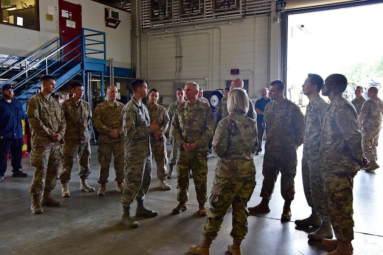 Air Force District of Washington Commander Maj. Gen. Ricky N. Rupp and AFDW Command Chief Master Sgt. Christopher Yevchak chat with Airmen from the 11th Logistics Readiness Squadron vehicle maintenace team Aug. 20. Rupp is visiting various units to better learn their missions and meet the people who accomplish them.