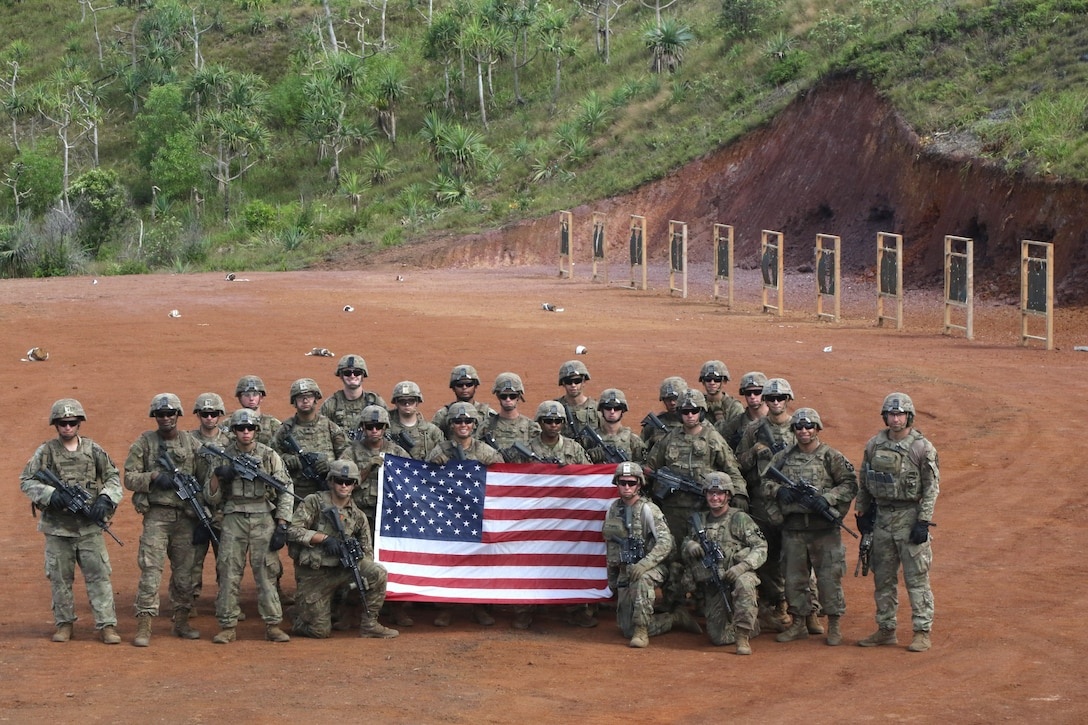Soldiers pose for a photo on a range holding a U.S. flag.
