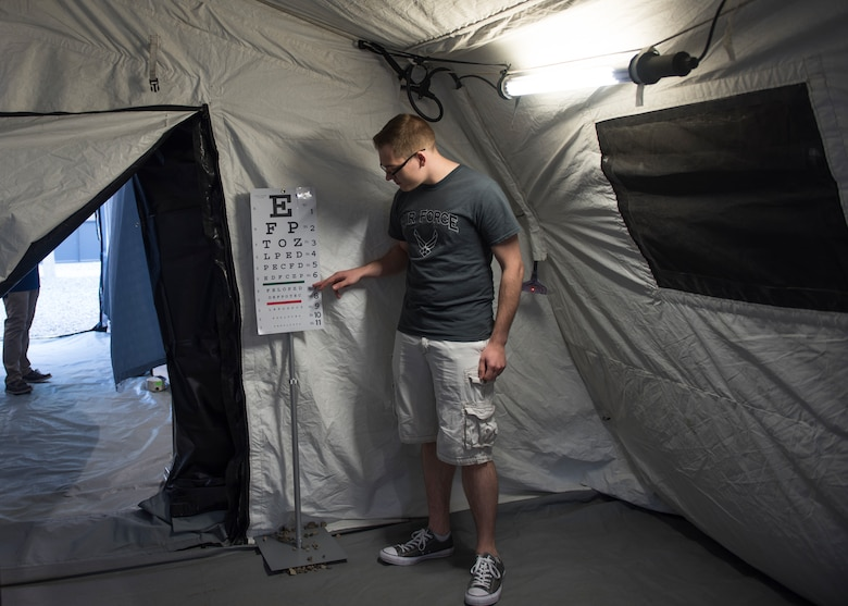 U.S. Air Force Staff Sgt. Daniel Jeppesen, 366th Healthcare Operations Squadron pediatric technician, points to a vision chart August 17, 2019, on Mountain Home Air Force Base, Idaho. Airmen and families were welcomed into the Air Transportable Clinic to recieve free medical physicals. (U.S. Air Force photo by Airman Natalie Rubenak)