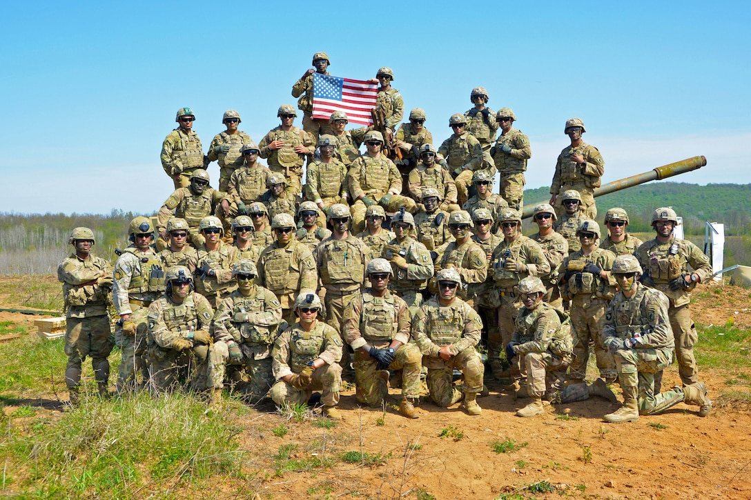 Soldiers pose for a photo and hold up a U.S. flag.