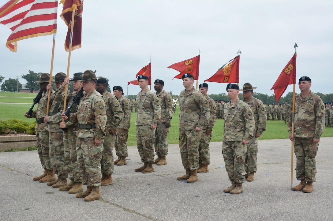 Soldiers, some holding flags, stand in formation on a paved area.
