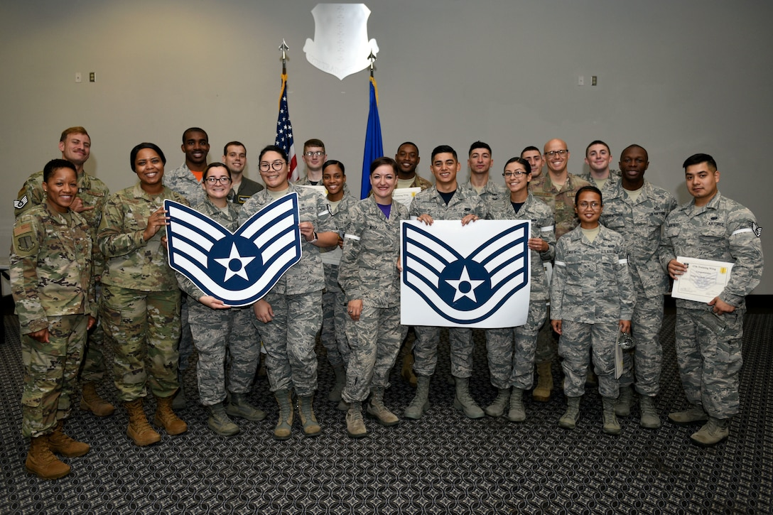U.S. Air Force staff sergeant selects pose for a photo with Goodfellow leadership during the staff sergeant release party at the event center on Goodfellow Air Force Base, Texas, August 23, 2019. Leadership and peers congratulated the selectees on their transition from junior enlisted Airmen to noncommissioned officers. (U.S. Air Force photo by Airman 1st Class Robyn Hunsinger/Released)