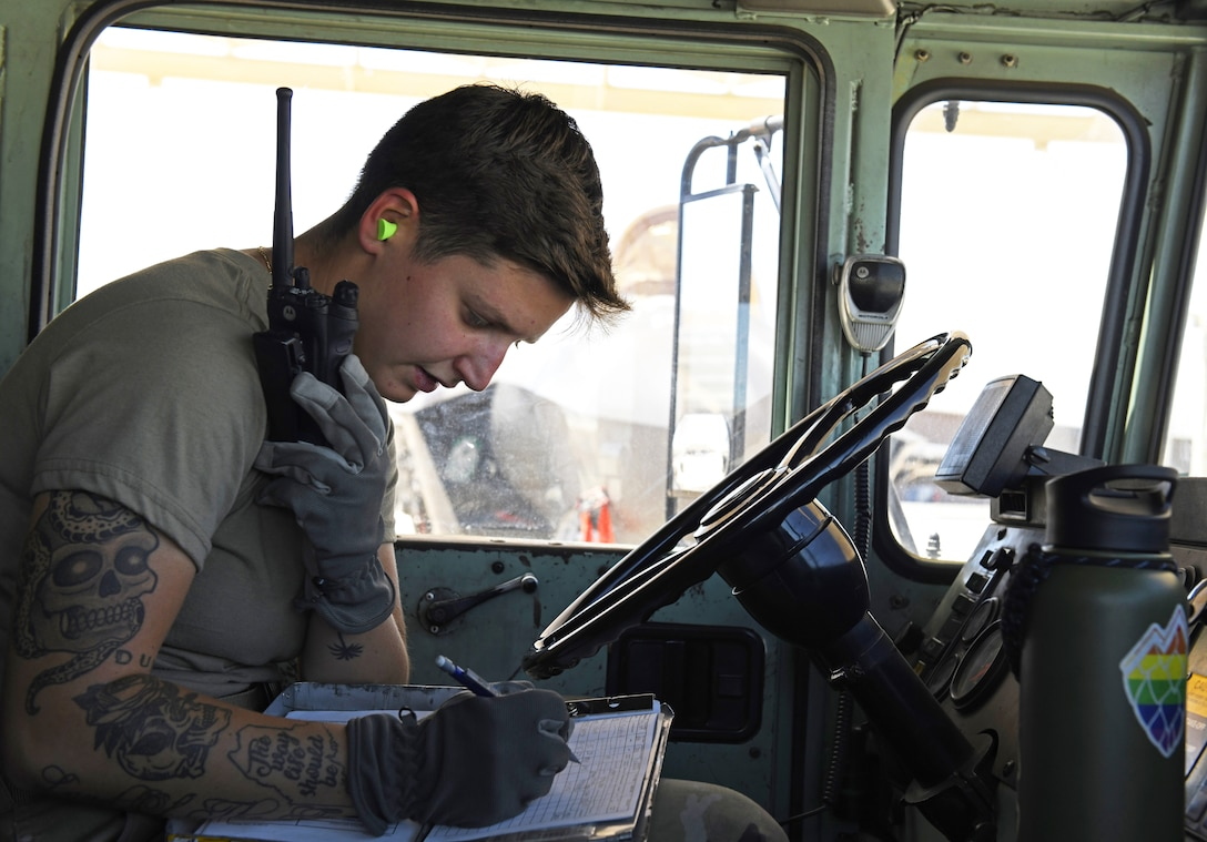 Airman 1st Class Katlynn Masnyk, 56th Logistics Readiness Squadron distribution fuels operator, sits in a R-11 Refueler and relays information over a radio while writing down statistics on a daily summary worksheet after refueling an F-35A Lightning II Aug. 21, 2019, at Luke Air Force Base, Ariz.