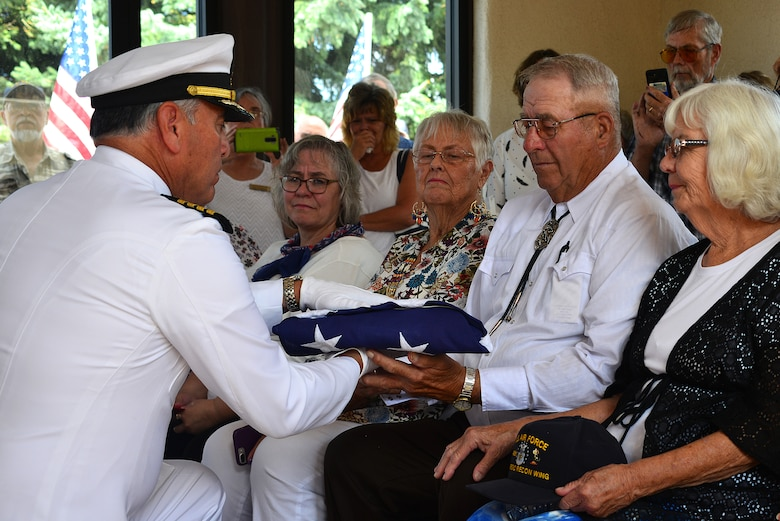 U.S. Navy Capt. Joseph Quintana, Navy Operational Support Center Albuquerque, presents a flag to Jerry Clark, nephew of U.S. Navy Fireman First Class Billy James Johnson, at the Santa Fe National Cemetery in Santa Fe, N.M. Aug. 19, 2019. Technological advances with mitochondrial DNA allowed his primary next of kin to provide a DNA sample which lead to positive identification of his uncle. Of the 429 Sailors that lost their lives on the USS Oklahoma during the attack on Pearl Harbor Dec. 7, 1941, only 35 were later positively identified with this advance technology. (U.S. Air Force photo by Airman 1st Class Austin J. Prisbrey)