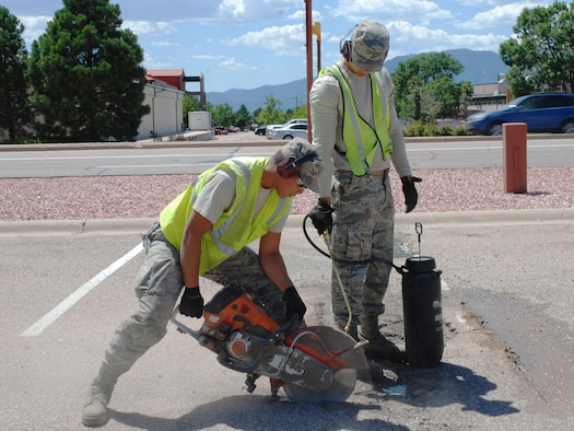Senior Airman Lemuel Travis, 21st Civil Engineering Squadron heavy equipment operator, left, and Senior Airman Daniel Acevedo-Chacon, 21st Civil Engineering Squadron heavy equipment operator, start repairs on a pothole, Aug. 15, 2019. While Travis operates a concrete saw, Acevedo-Chacon sprays it with water to prevent overheating. It takes hard work and diligence to keep the roads clear and in good repair on Peterson Air Force Base, Colorado, but that's what Dirt Boyz Travis and Acevedo-Chacon do. (U.S. Air Force Photo by Griffin Swartzell)