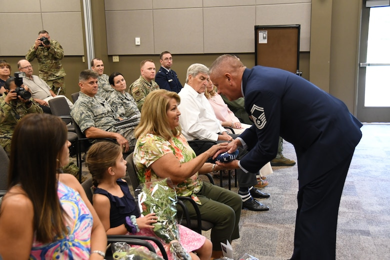 "Senior Master Sgt. William Bassett retired from the 932nd Airlift Wing in a ceremony held August 4, 2019 at Scott Air Force Base, Ill.  He was presented the American flag which he presented to his family,  He took a few moments to thank everyone, looked at a list of all the generals he's served under, and touched on the legacy of the 932nd Airlift Wing that he's been a part of since 2005. ""Always dream big, and always be a good mentor. It means something. There are so many friends you meet along the way, but they have no idea how much they impacted your life, and you can impact someone's life too,"" Bassett said. (U.S. Air Force photo by Lt. Col. Stan Paregien)"
