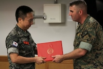 U.S. Marine Corps Forces Korea (MARFORK) honors Captain Ko Hyun Jong for serving as the Republic of Korea Marine Corps Liaison Officer to MARFORK Aug. 26. Capt. Ko plays a critical role in assisting MARFORK during operations by serving as a vital link between two staffs from two separate nations. Liaison Officers from both the U.S. Marine Corps and ROK Marine Corps continue the tradition of brotherhood between the two services and build upon the ROK-US Alliance that has stood for over 70 years. (U.S. Marine Corps Photo by Sgt. Paker Golz)