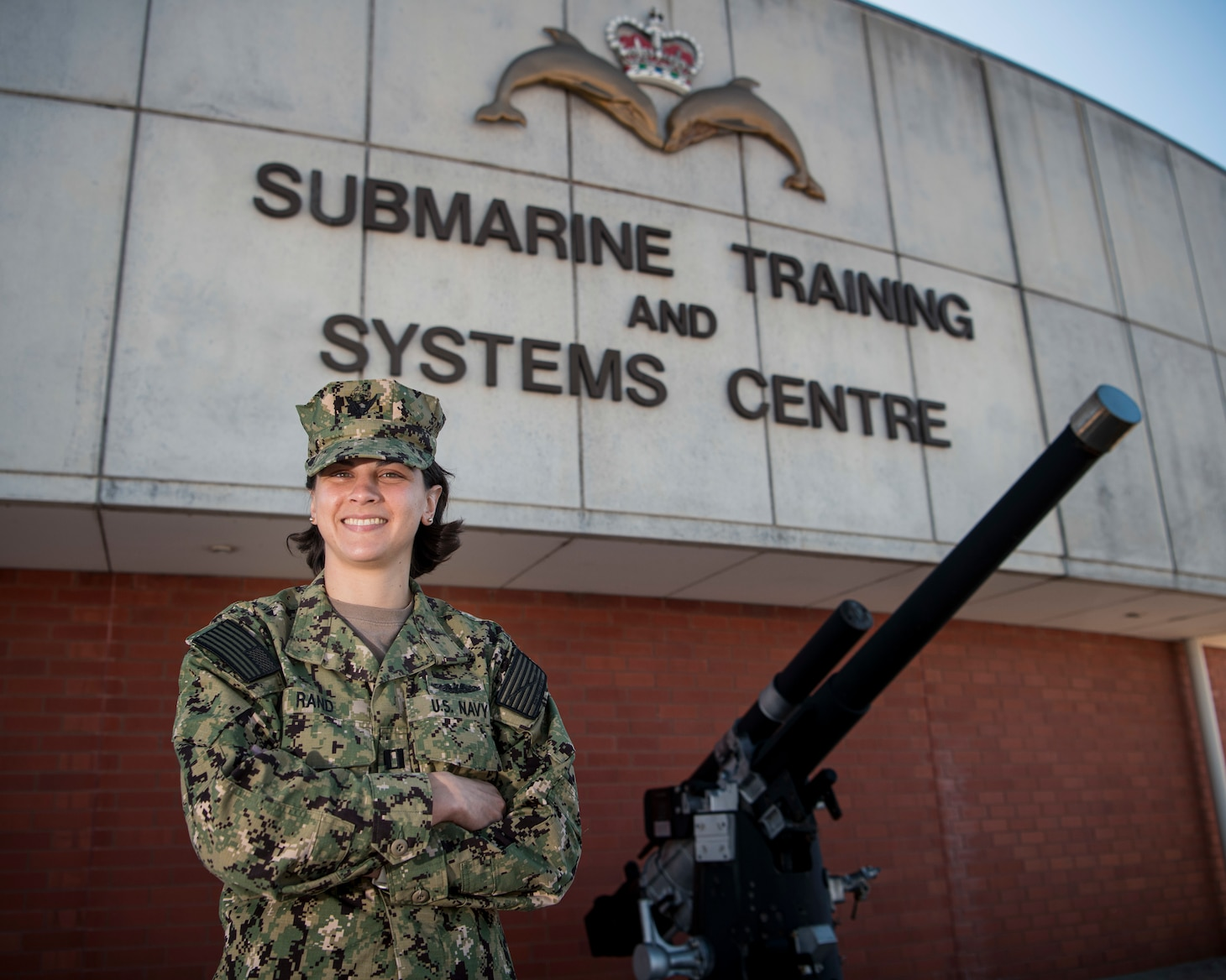 "A female Sailor smiles while posing for a photo in front of a brick building with the words ""Submarine Training and Systems Centre"" written on the building."