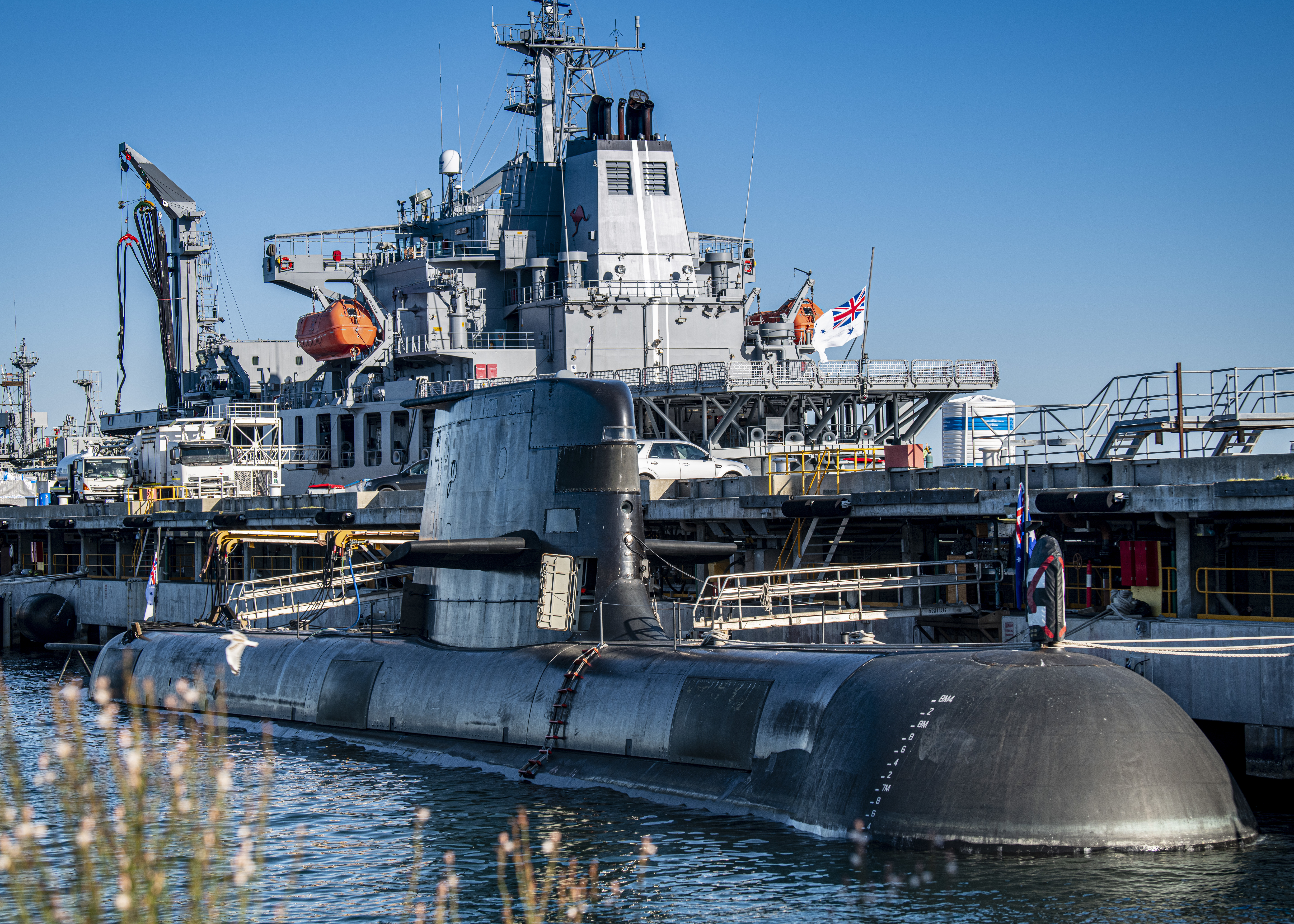 A Collins-class guided missile submarine is moored pier-side during daylight