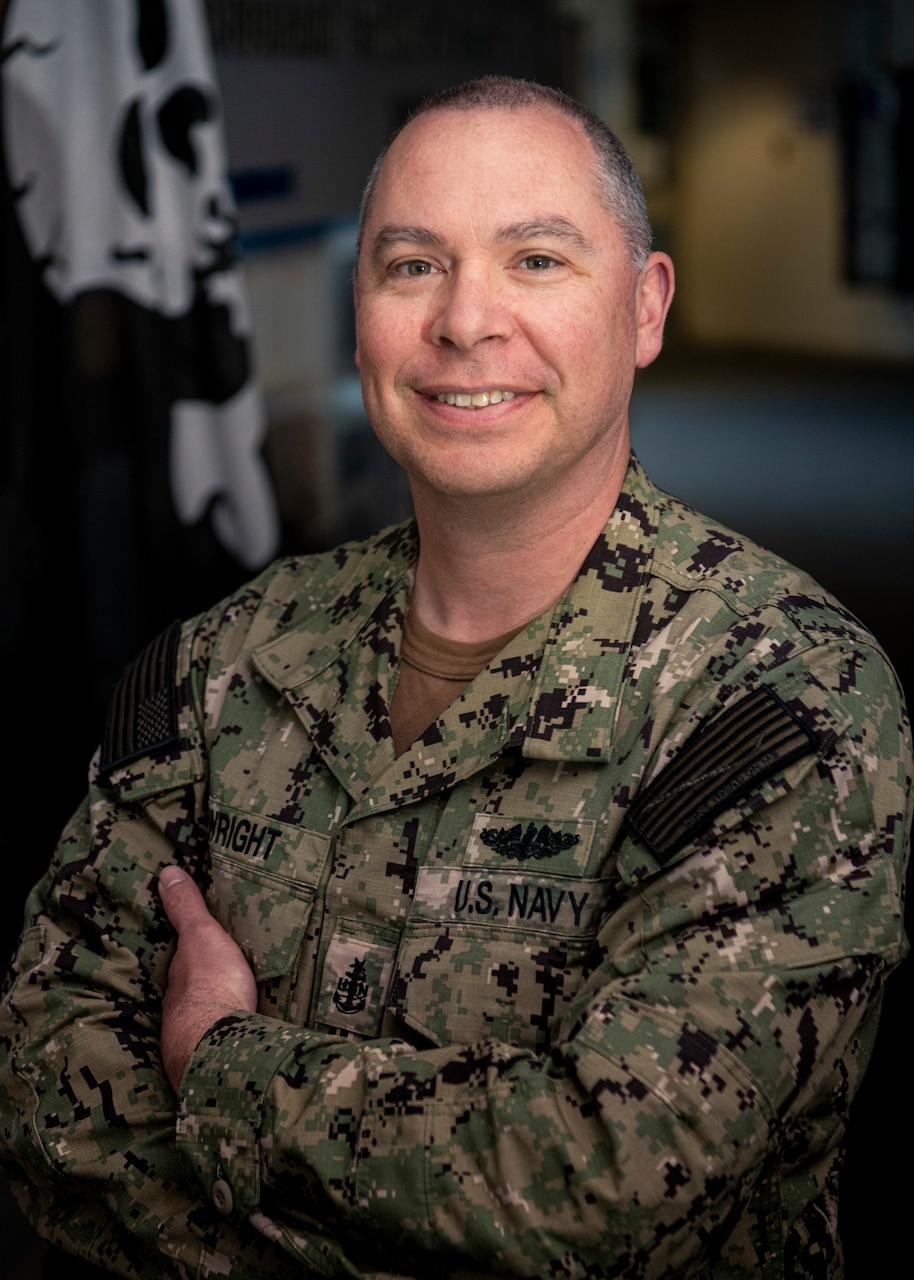 A male Navy Sailor stands with his arms folded, smiling for a photo in uniform.