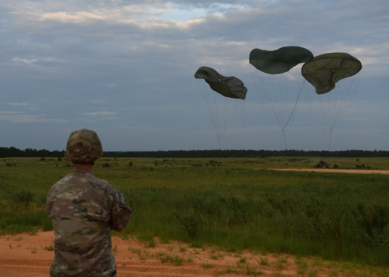 A U.S. Army Soldier assigned to the 82nd Airborne Division monitors equipment being airdropped onto a landing zone during Battalion Mobility Tactical Week at Fort Bragg, N.C., Aug. 20, 2019. Battalion Mass Tactical Week is a joint exercise involving the U.S. Air Force and the U.S. Army designed to enhance service members' abilities by practicing contingency operations in a controlled environment. The exercise incorporated three C-130J Super Hercules assigned to Little Rock Air Force Base, Arkansas, three C-17 Globemaster IIIs assigned to Joint Base Charleston, S.C. and Army paratroopers assigned to the 82nd Airborne Division of Fort Bragg, N.C. The exercise allowed all parties to quickly and safely complete training tasks, such as personnel and cargo air drops, to prepare joint forces to operate during global mobility missions.