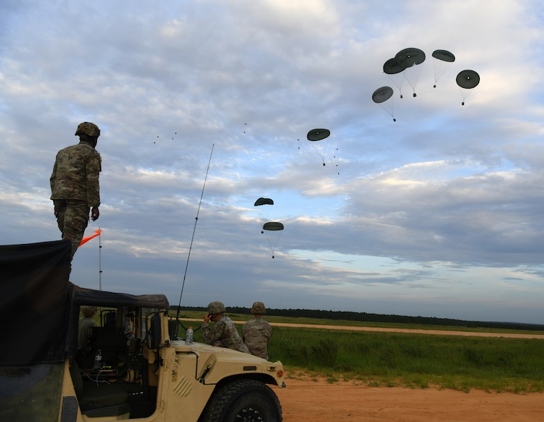 U.S. Army Soldiers assigned to the 82nd Airborne Division monitor equipment being airdropped onto a landing zone by C-17 Globemaster III's from Joint Base Charleston during Battalion Mobility Tactical Week at Fort Bragg, N.C., Aug. 20, 2019. Battalion Mass Tactical Week is a joint exercise involving the U.S. Air Force and the U.S. Army designed to enhance service members' abilities by practicing contingency operations in a controlled environment. The exercise incorporated three C-130J Super Hercules assigned to Little Rock Air Force Base, Arkansas, three C-17 Globemaster IIIs assigned to Joint Base Charleston, S.C. and Army paratroopers assigned to the 82nd Airborne Division of Fort Bragg, N.C. The exercise allowed all parties to quickly and safely complete training tasks, such as personnel and cargo air drops, to prepare joint forces to operate during global mobility missions.