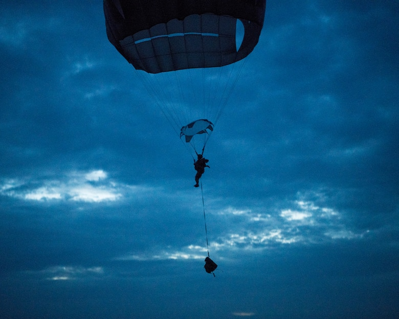 A paratrooper assigned to the 82nd Airborne Division descends onto a landing zone at lowlight conditions during Battalion Mobility Tactical Week at Fort Bragg, N.C., Aug. 20, 2019. Battalion Mass Tactical Week is a joint exercise involving the U.S. Air Force and the U.S. Army designed to enhance service members' abilities by practicing contingency operations in a controlled environment. The exercise incorporated three C-130J Super Hercules assigned to Little Rock Air Force Base, Arkansas, three C-17 Globemaster IIIs assigned to Joint Base Charleston, S.C. and Army paratroopers assigned to the 82nd Airborne Division of Fort Bragg, N.C. The exercise allowed all parties to quickly and safely complete training tasks, such as personnel and cargo air drops, to prepare joint forces to operate during global mobility missions.
