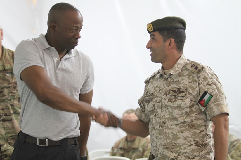 U.S. Army Lt. Col. Omar Minott, left, the commander of 1st Squadron, 102nd Cavalry Regiment, 44th Infantry Brigade Combat Team, New Jersey Army National Guard, shakes hands with Jordanian Armed Forces Lt. Col. Saif Al Khawaldeh, the commander of the 39th Mechanized Infantry Battalion, prior to a planning meeting for Exercise Eager Lion 19 in Jordan on Aug. 19, 2019. This multinational exercise is U.S. Central Command's premiere exercise in the Levant region and is a major training event that provides U.S. forces, Jordan Armed Forces and 28 other participating nations the opportunity to improve their collective ability to plan and operate in a coalition-type environment.