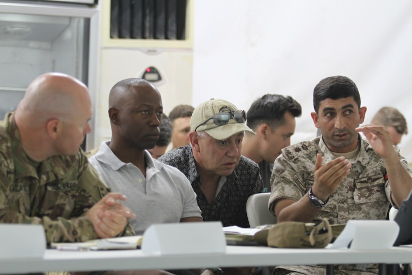 From left, U.S. Army Maj. Erick Malaske, operations officer, 1st Battalion, 68th Armor Regiment, 3rd Armored Brigade Combat Team, 4th Infantry Division, Task Force Spartan; Lt. Col. Omar Minott, commander, 1st Squadron, 102nd Cavalry Regiment, 44th Infantry Brigade Combat Team, New Jersey Army National Guard; Jordanian Armed Forces Lt. Col. Saif Al Khawaldeh, commander, 39th Mechanized Infantry Battalion; discuss upcoming operations for exercise Eager Lion 19. This multinational exercise is U.S. Central Command's premiere exercise in the Levant region and is a major training event that provides U.S. forces, Jordan Armed Forces and 23 other participating nations the opportunity to improve their collective ability to plan and operate in a coalition-type environment.