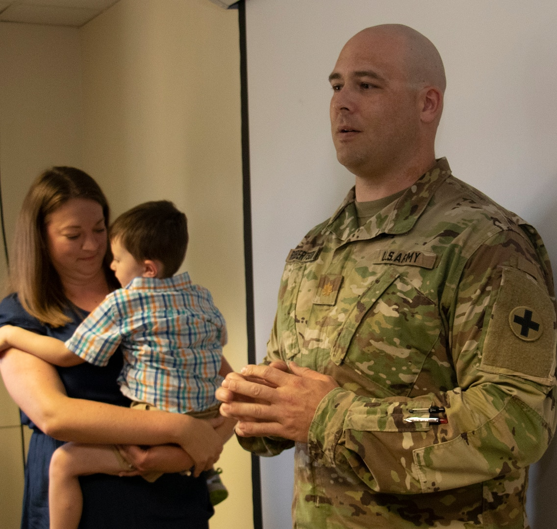 Newly promoted Maj. Shawn Robertson, joined by wife, Sarah, and son, Reid, addresses friends attending his promotion ceremony, Aug. 23.