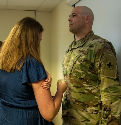 Newly promoted Maj. Shawn Robertson's wife, Sarah, places his new rank on his uniform during a promotion ceremony Aug. 23.