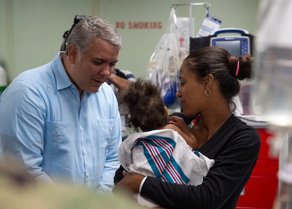 Colombian President Ivan Duque interacts with a baby.