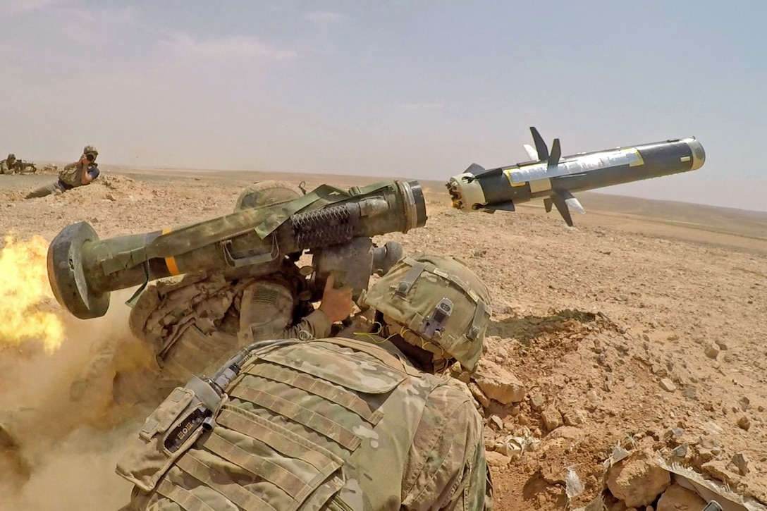 Soldiers fire a missile in the desert.