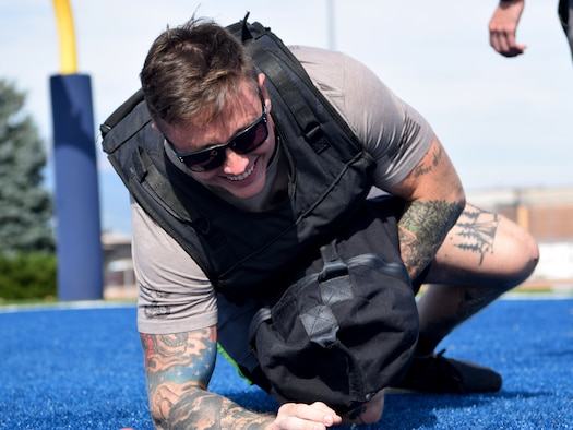 """The 21st Civil Engineering Squadron's Explosive Ordnance Disposal team members like Staff Sgt. Lawrence Gress, 21st CES EOD team member, pictured Aug. 23, 2019, train by doing """"The Gruester."""" The Gruester is an exercise that involves sprinting, rolling and pushups with a 30-pound vest and a 50-pound bag. Gress compared the group's constant, rigorous training to playing team sports. That's what he says it takes to stay proficient and effective for when the group is called out to address a potential explosive threat. (U.S. Air Force photo by Griffin Swartzell)"""