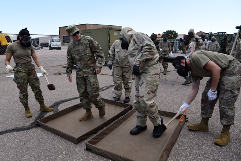 Tech. Sgt. Cody West, second to left, 21st Civil Engineering Squadron emergency management operations non-commissioned officer-in-charge, teaches his students how to decontaminate during a chemical, biological, radiological, nuclear and high-yield explosive class Aug. 22, 2019 at Peterson Air Force Base, Colorado. There are four phases that emergency management specialists are trained for: prepare, respond, mitigate and recover. (U.S. Air Force photo by Staff Sgt. Alexandra M. Longfellow)
