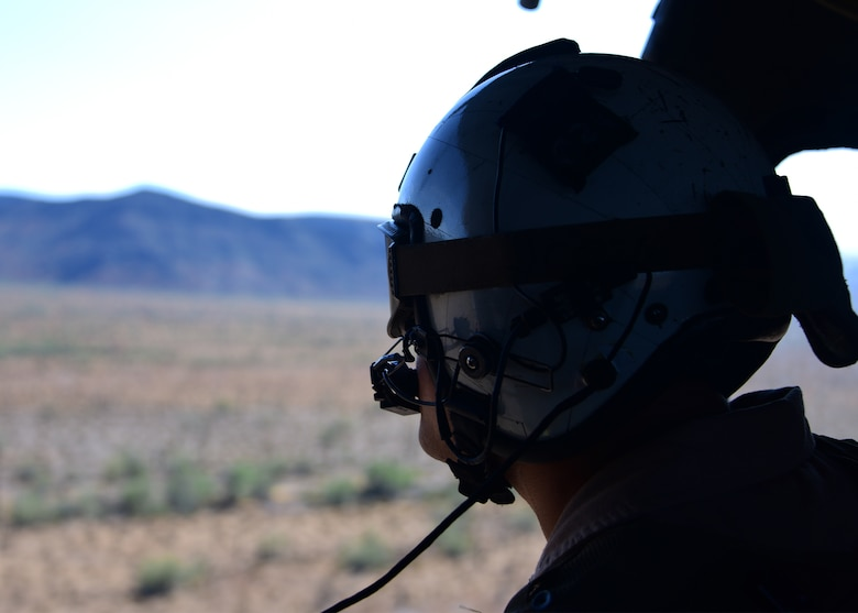 A U.S. Navy sailor looks out the side of an MH-60S Seahawk over Southern Arizona during Red Flag-Rescue 19-2 on Aug. 21, 2019. Davis-Monthan Air Force Base Airmen teamed up with Sailors, Marines and Soldiers for nearly three weeks to execute the Department of Defense's premier search and rescue exercise ensuring the DoD continues to develop into a faster, smarter and more lethal force. (U.S. Air Force photo by Airman 1st Class Jacob T. Stephens)