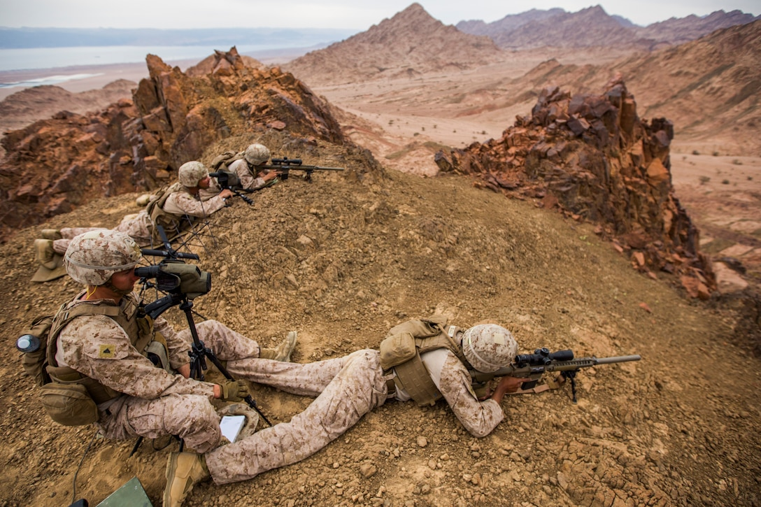 Marines fire rifles from the top of a cliff.