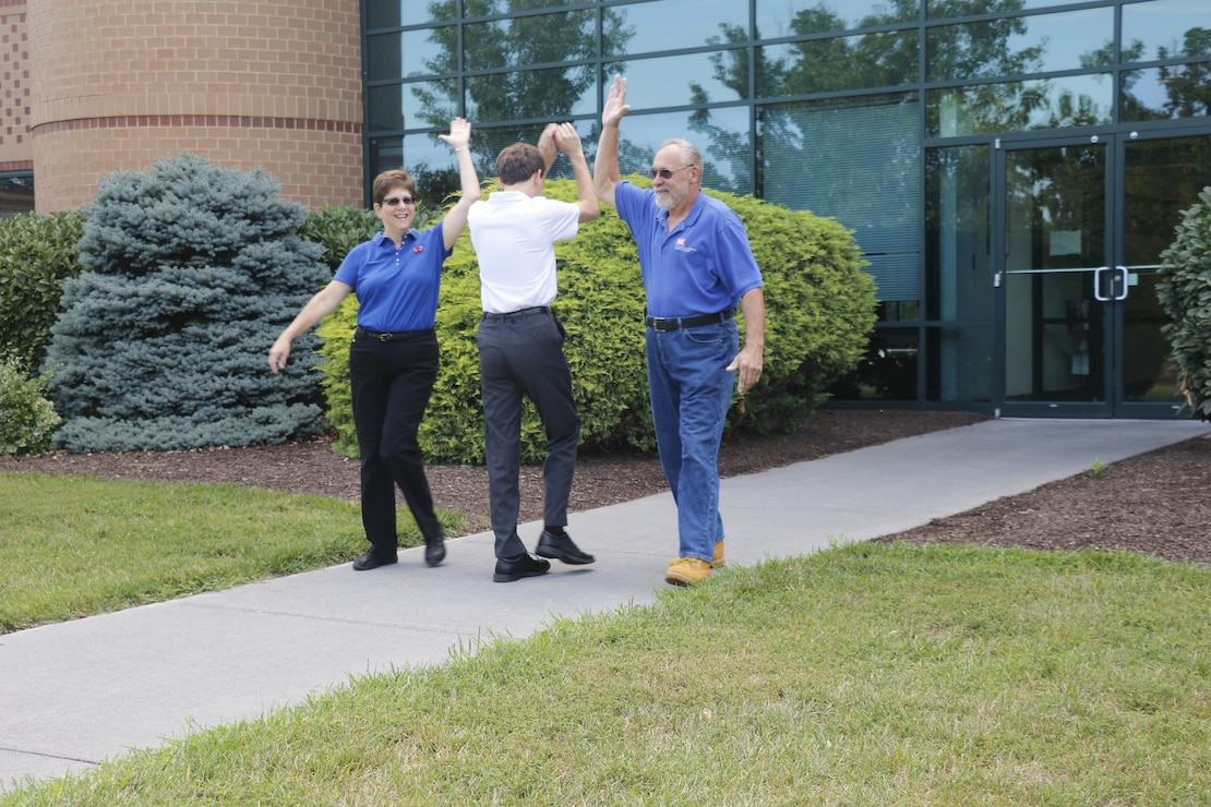 Carol and Bob Hickel high-five their son David Hickel as they leave the Middle East District Headquarters in Winchester, Va., and David, a summer intern with the District, enters. Carol is working as a rehired annuitant and Bob is preparing to retire after a 10-year career with the District.