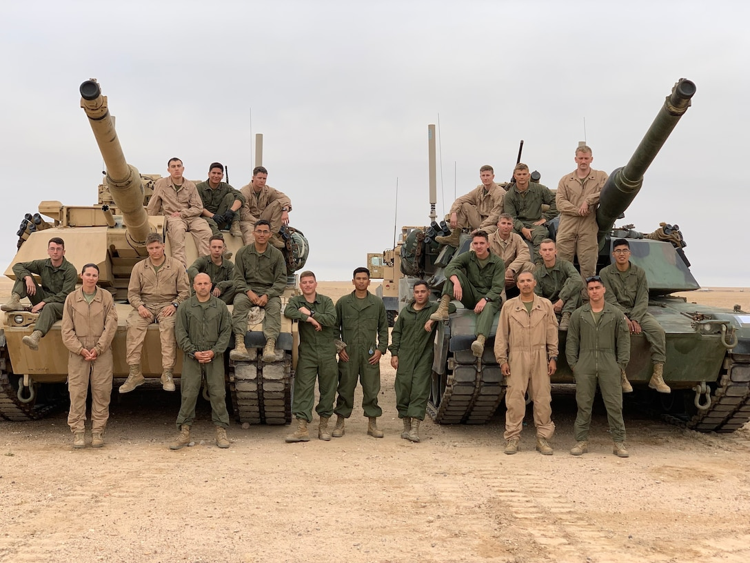 A large group of Marines pose for a picture on top of two tanks.